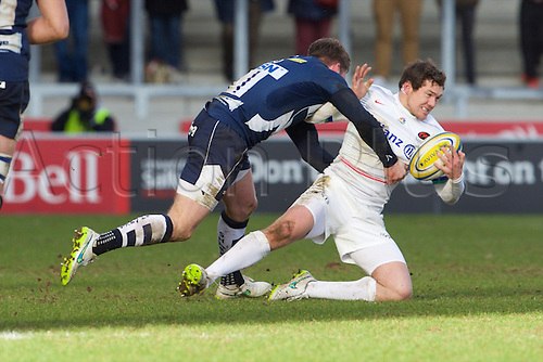 21.02.2015.  Sale, England.  Aviva Premiership Rugby. Sale Sharks versus Saracens. Saracens fullback Alex Goode is tackled by Sale Sharks wing Mark Cueto.