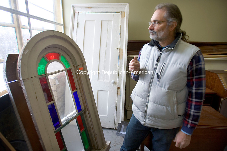 HAMDEN, CT. 06 January 2011-010611SV02--Joe DeRisi of Urbanminers looks over an antique stained glass window his company rescued from a building they worked in Hamden Tuesday.<br /> Steven Valenti Republican-American