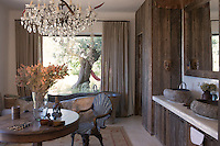The ensuite bathroom is an eclectic combination of natural finishes with rough wooden cupboards and stone bath and sinks