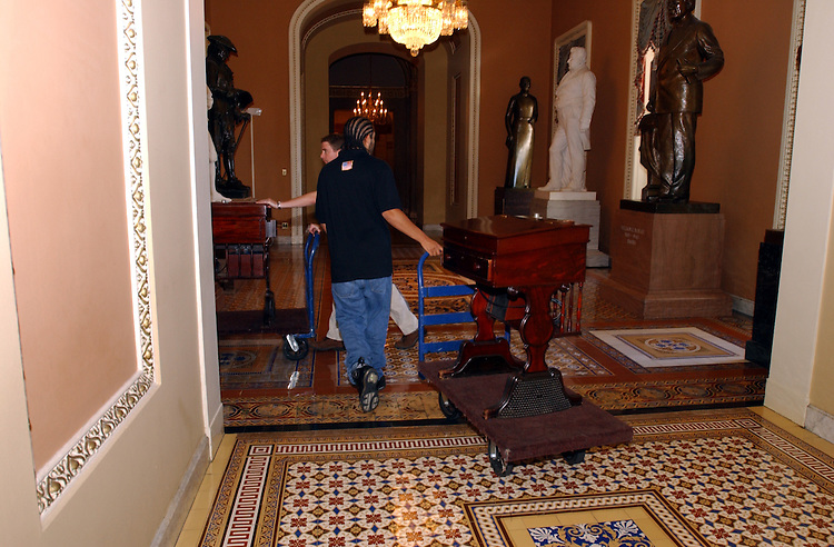 carpet4_080802 -- Workers move the desk from the floor of the Senate floor of the U.S. Capitol so new carpet can be installed.
