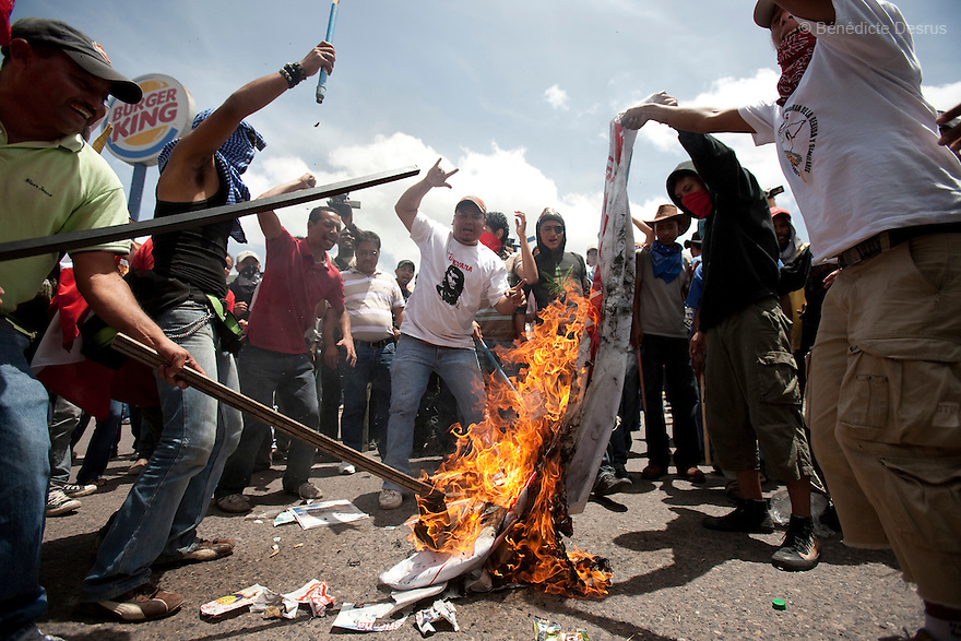 4 July 2009 - Tegucigalpa, Honduras  Supporters of ousted Honduran President Manuel Zelaya burn a banner with an image of interim Honduras' President Roberto Micheletti during a protest march near the presidential residence in Tegucigalpa, capital of Honduras. Zelaya has been forced into exile after being arrested by a group of soldiers in an apparent military coup. Zelaya was warned he would be arrested if he return to Honduras but has vowed to return to Honduras on Sunday accompanied by Latin American leaders. Photo credit: Benedicte Desrus
