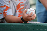 A fan holds an autographed baseball prior to the game between the Great Falls Voyagers and the Ogden Raptors on July 17, 2014 at Lindquist Field in Ogden, Utah. (Stephen Smith/Four Seam Images)