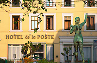 A statue of an angel seen from behind with up stretched arm, in bronze, in the background the Hotel de la Poste  Vienne, Isère Isere, France, Europe