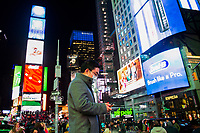 "NEW YORK, NEW YORK - MARCH 5: A man wears a face mask as he checks his phone at Times Square on March 5, 2020. in New York City. NY state has 44 people under quarantine,  About 4,000 people are under ""precautionary"" quarantine in more than two dozen counties, including more than 2,700 in the city and 1,000 in Westchester, Cuomo said. (Photo by Pablo Monsalve/VIEWpress via Getty Images)"