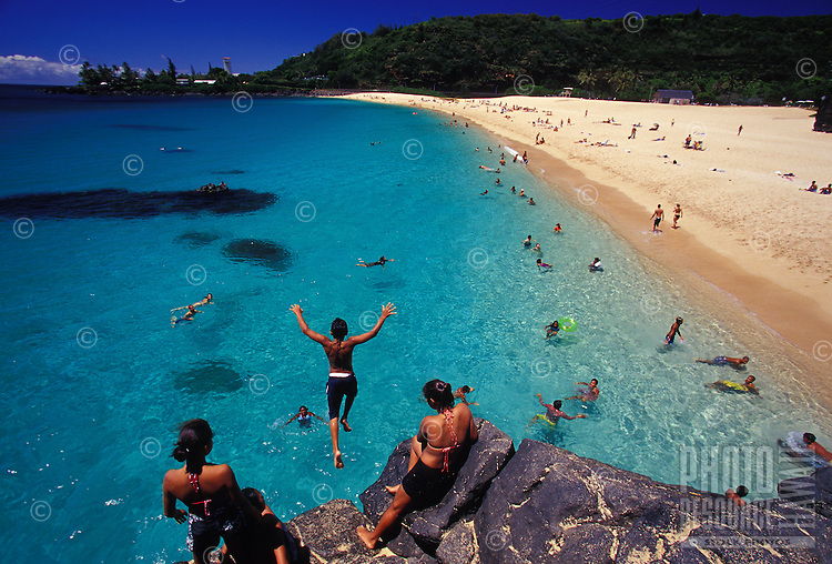 Waimea Bay beach with clear blue water and people standing on rocks, North Shore of Oahu, Hawaii