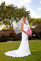 Full length of bride with bouquet, smiling with veil blowing in the wind