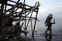 A fisherman carries bags of mussels, recently caught in the bay off of Jakarta. As a result of severe levels of water pollution in the bay, the mussels are now laced with toxins, ingested as the filter-feeders try to gather nutrients from the surrounding waters. The bay's toxicity has led to many fisherman being unable to sell seafood, resulting in large amounts of unemployment and continued health concerns.