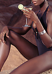 Sexy black woman holding a martini glass with iced cocktail, artistic photo, closeup of sensual body