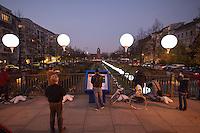 """In Berlin begann am Freitag den 7. November 2014 entlang des ehemaligen Mauerverlaufs eine Lichtinstallation als """"Symbol der Hoffnung für eine Welt ohne Mauern"""". Aus etwa achttausend  beleuchteten und mit Helium gefuellten Luftballons entstand eine Lichtgrenze, die 15 Kilometer durch die Berliner Innenstadt fuehrt.<br /> Am Sonntag den 9. November sollen tausende der Ballons u.a. am Brandenburger Tor in die Luft steigen.<br /> Im Bild: Die Lichtinstallation am ehemaligen Todesstreifen zwischen den Berliner Stadtteilen Kreuzberg in Westberlin (rechts der Ballons) und Mittein Ostberlin (links der Ballons). Der Todesstreifen ist heute ein Park mit See und Cafe.<br /> 7.11.2014, Berlin<br /> Copyright: Christian-Ditsch.de<br /> [Inhaltsveraendernde Manipulation des Fotos nur nach ausdruecklicher Genehmigung des Fotografen. Vereinbarungen ueber Abtretung von Persoenlichkeitsrechten/Model Release der abgebildeten Person/Personen liegen nicht vor. NO MODEL RELEASE! Don't publish without copyright Christian-Ditsch.de, Veroeffentlichung nur mit Fotografennennung, sowie gegen Honorar, MwSt. und Beleg. Konto: I N G - D i B a, IBAN DE58500105175400192269, BIC INGDDEFFXXX, Kontakt: post@christian-ditsch.de<br /> Urhebervermerk wird gemaess Paragraph 13 UHG verlangt.]"""