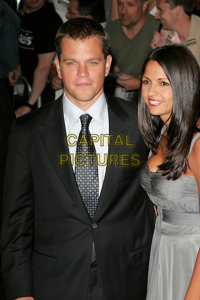 "MATT DAMON & LUCIANA BARROSO.UK premiere of ""The Bourne Ultimatum"", Odeon Leicester Square, London, England..August 15th, 2007.half length black suit grey gray dress married husband wife.CAP/AH.©Adam Houghton/Capital Pictures"
