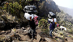Mt. Kilimanjaro, Tanzania -- July 22, 2010 --On day two of the trek, two porters carries a heavy load over his head. Porters are hired by trekking companies and earn around $20-$30 for a six-day trip. (Razan Alzayani / The National) Travel Story