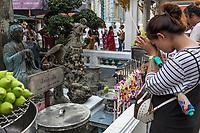 Bangkok, Thailand.  Worshiper Praying to Goddess of Mercy Kun Iam, at the Royal Grand Palace.