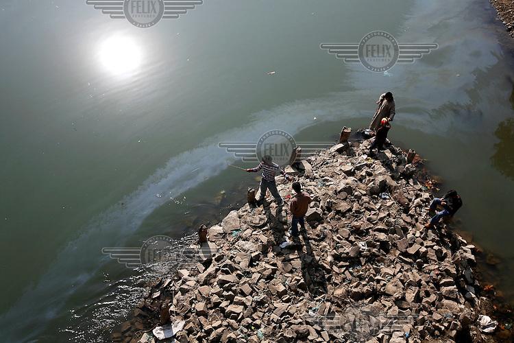 Young boys fish in Jehlum River (or Jhelum River). The river is polluted. Srinagar, Kashmir, India. © Fredrik Naumann/Felix Features