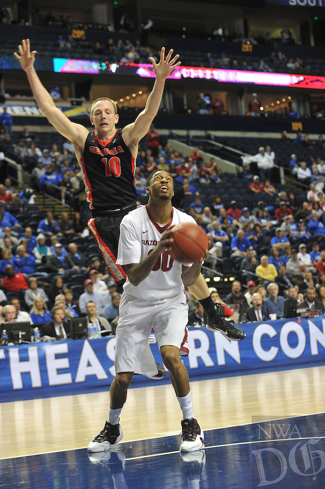 NWA Democrat-Gazette/Michael Woods --03/14/2015--w@NWAMICHAELW... University of Arkansas guard Rashad Madden pulls up for a ump shot in front of Georgia defender Taylor Echols during the second half of the Razorbacks 60-49 win in Saturdays game against the Georgia Bulldogs at the 2015 SEC basketball tournament at Bridgestone Arena in Nashville.