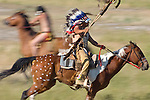 An Indian Chief is captured on horseback in full regalia during battle at the annual Custer Battle of the Little Bighorn reenactment in Hardin Montana. Model Release
