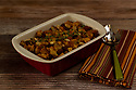 Baked bread stuffing with thyme in a red ceramic baking pan