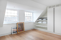 A white attic bedroom with built in shleving and cupboard with a wooden floor.