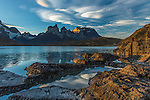 Wide-angle view of  the Cuernos del Paine and Monte Almirante Nieto with rocks and Lake Pehoe in the foreground.  Lenticular clouds are beginning to form over the peaks.  Torres del Paine National Park in Patagonia, Chile.  A UNESCO World Biosphere Reserve. The Cuernos and clouds are reflected on the lake surface.