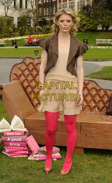 EMILIA FOX.The launch of the Galaxy Irresistible Reads campaign to give away 1 million books, Embankment Gardens, London, England..March 23rd, 2009.full length reading brown jacket beige skirt pink tights yellow gold peep toe shoes couch sofa dress.CAP/CAN.©Can Nguyen/Capital Pictures.