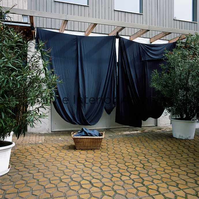 Lengths of blue dyed fabric hang outside Sabine Fajana's studio where she creates the homeware items including linen, lights, blankets, and rugs, which she sells under her brand VIVIDGREY