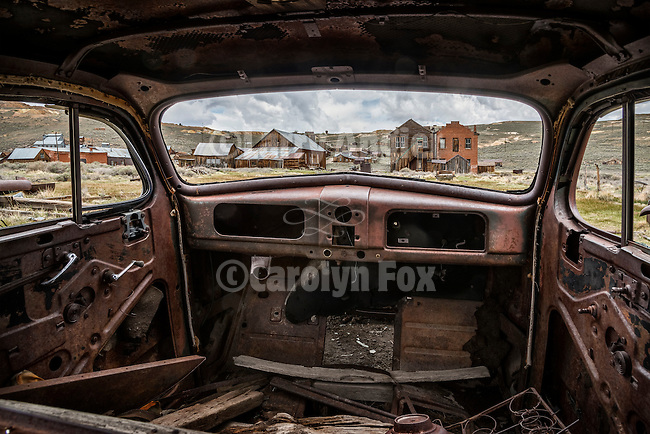 The old town of Bodie through the window of a rusty 1930s Pontiac coupe. Bodie State Historic Park, California.