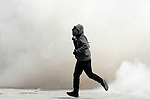 Protesters throw stones to riot police and the police answer with tear gas during a demonstration against the new austerity measures.