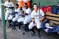 Robert Refsnyder (15) of the Charleston RiverDogs sits in the dugout seated next to Yeicok Calderon (25) and Kelvin De Leon (35) before a game against the Greenville Drive on Saturday, April 6, 2013, at Fluor Field at the West End in Greenville, South Carolina. Charleston won Game 1 of a doubleheader, 6-2. (Tom Priddy/Four Seam Images)
