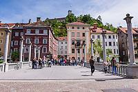 Ljubljana. People walking across the Cobblers Bridge towards Ljubljana Castle, Slovenia, Europe