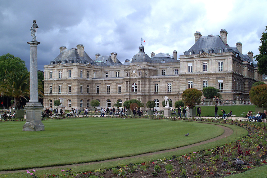 People walk and sit in Luxembourg Gardens in front of the Luxembourg Palace, Paris, on a cloudy day.