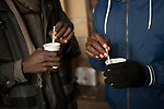 Two African migrants take hot milk sheltered from the cold under the arches of Irun City Council. Irun (Basque Country). Ocotber 28, 2018. A group of volunteers has created a host network to serve migrants and inform about the public services they are entitled to and the ways to cross the border. This group of volunteers is avoiding a serious humanitarian problem Irun, the Basque municipality on the border with Hendaye. As the number of migrants arriving on the coasts of southern Spain incresead, more and more migrants are heading north to the border city of Irun. French authorities have reacted by conducting random checks as far as the city of Bordeaux, more than 200 kilometers north of the border. Migrants who are caught are then deported back to Irun. (Gari Garaialde / Bostok Photo).