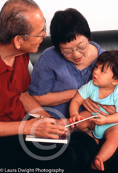 10 month old baby boy interaction with grandparents listening to them read board book language development vertical
