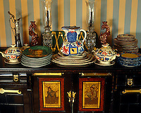 Close up of a collection of antique tableware with a pair of glass candleholders and two ceramic figurines