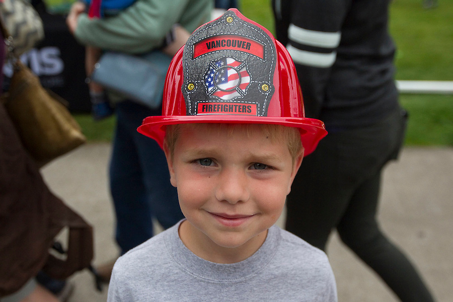"Owen Conner, 6 wears a plastic fire helmet at ""Fire in the Park""  in Vancouver Saturday July 16, 2016. Fire in the Park is the annual informational and charitable event hosted in Esther Short Park by the Vancouver Firefighters Union. It's a day of fire-safety and first-aid education for children and families — as well as fundraising for the victims of the real emergencies that firefighters respond to every day. (Photo by Natalie Behring/ for the The Columbian)"