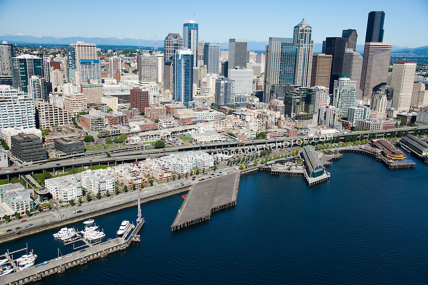 An aerial view of the downtown Seattle waterfront skyline, and middle and northern portions of the Alaskan Way viaduct / Highway 99 at the Seattle Aquarium and Belltown on a sunny summer day.