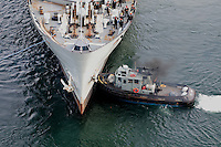 Navy ship being pushed by a tug boat