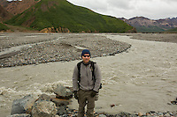 Dave stands in front of the Toklat River in Denali National Park. The river is glacial melt and carries silt, making the water a murky dark gray color.