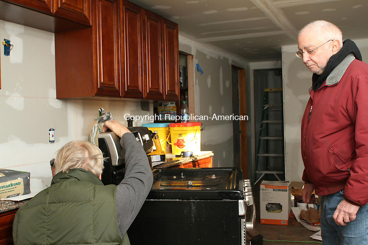 WATERTOWN, CT, 25 November, 2015 - 112515LW03 - From left, volunteers Steve Poole and Dan Zeno install a gas stove in the White family's kitchen on Lancaster Steet in Watertown Wednesday. The volunteers worked for the past month to renovate the kitchen in time for the Whites to enjoy an early Christmas at home Saturday before Xander White, 4, goes to the hospital for cancer treatments. <br /> Laraine Weschler Republican-American