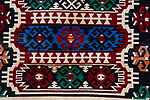 A woven Bedouin rug for sale in the ruins of the Nabataean city of Petra in the Hashemite Kingdom of Jordan.  Petra Archeological Park is a Jordanian National Park and a UNESCO World Heritage Site.