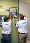 Anthony Pennington, left, and Denton Guthrie hang the photo of Gerri Botte, Ph. D., on the third floor of Alden Library. ©Ohio University / Photo by Kaitlin Owens