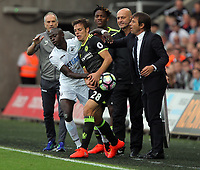 Cesar Azpilicueta of Chelsea (C) and manager of Chelsea, Antonio Conte (R) snatch the ball from Modou Barrow of Swansea City during the Premier League match between Swansea City and Chelsea at The Liberty Stadium on September 11, 2016 in Swansea, Wales.