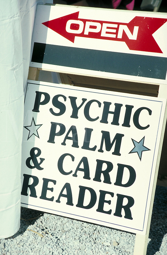 Sandwich board sign reads - open, psychic palm and card reader.