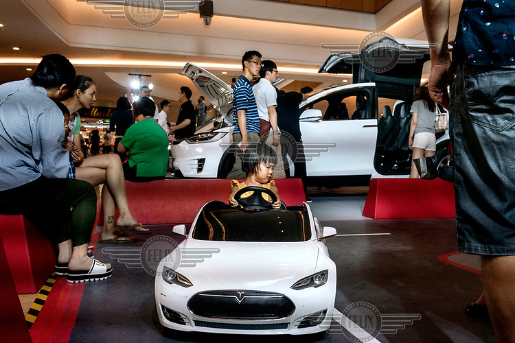 A child rides a toy Tesla as people look at a Tesla Model X , behind, on a Tesla stand at a promotional event in the Indigo shopping mall.