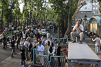 A man watches from atop a bus shelter as an estimated one million people form a human chain along Vali asr Avenue, the longest street in Tehran. Following a disputed election result, thousands of supporters of opposition candidate Mir-Hossein Mousavi took to the streets in protest.