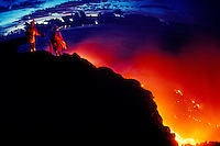 Two people stand on a cliff overlooking red and orange molten lava of Kilauea.