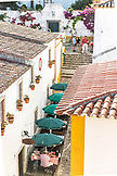 PORTUGAL, Obidos, People are dining in an outdoor restaurant, sitting under Green Umbrellas