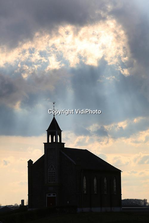 Foto: VidiPhoto<br /> <br /> HOMOET - Donkere wolken pakken zich samen boven het kleine hervormde kerkje in het buurtschap Homoet. Ook letterlijk. Uit het inspectierapport van Monumentenwacht Gelderland aan de hervormde gemeente maandag, blijkt dat de in 2010 herstelde voegen weer beginnen uit te slijten. De inspectiedienst spreekt van &quot;kwalitatief minder deugdelijk werk&quot; aan de zuidgevel door de aannemer. Ook is er sprake hernieuwde scheurvorming bij de toren. De westgevel is er nog slechter aan toe. Daar heeft de aannemer er helemaal een potje van gemaakt, zo blijkt. Achter de stootvoegen blijken forse holtes aanwezig en opnieuw uithakken en voegen is noodzakelijk. Volgens Monumentenwacht is er ronduit slecht werk geleverd en dient dit met spoed hersteld te worden. Het terpkerkje van Homoet is een van de kleinste kerkjes van ons land en dateert van 1869. Het diende in het begin van de 19e eeuw als 'vluchtheuvel' voor boeren bij hoogwater. Het is het enige zogenoemde waterstaatskerkje in de Over-Betuwe dat er nog is. Slechts eenmaal in de maand wordt er nog een kerkdienst gehouden. In het gebouw werd onlangs ingebroken.