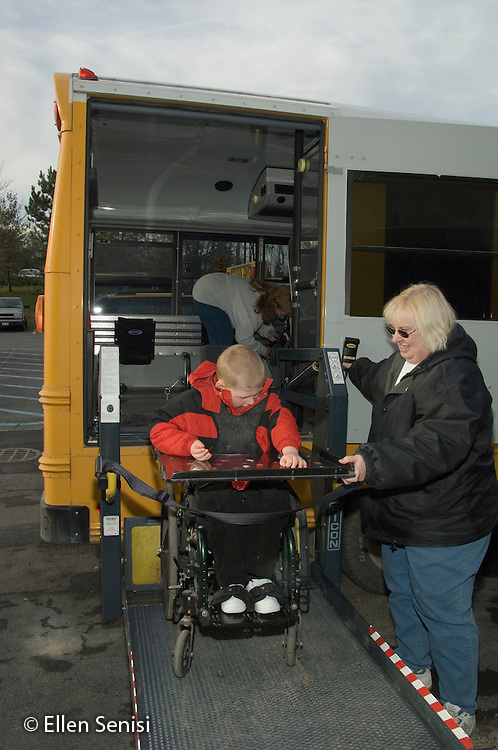 MR / Albany, NY.Langan School at Center for Disability Services .Ungraded private school which serves individuals with multiple disabilities.Child boards schoolbus using wheelchair lift. Bus driver operates lift. Boy: 9, cerebral palsy, non verbal with expressive and receptive language delays.MR: Law4, Zie1.© Ellen B. Senisi