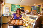 An employee holding a basket of freshly baked bread at Waves of Grain Bakery in Cannon Beach