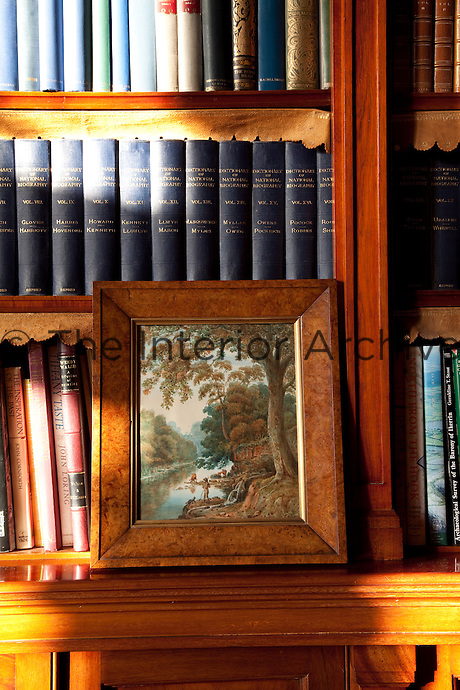 A detail of a bookcase showing the strips of embossed leather ornamenting the shelves