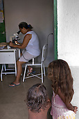 Xingu, Volta Grande,  Pará State, Brazil. Aldeia Paquissamba (Juruna). A nurse checks for malaria through a microscope.